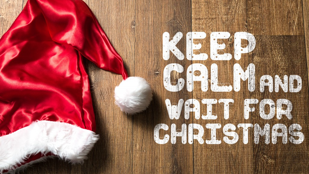 Keep Calm and Wait For Christmas written on wooden background with Santa Hat